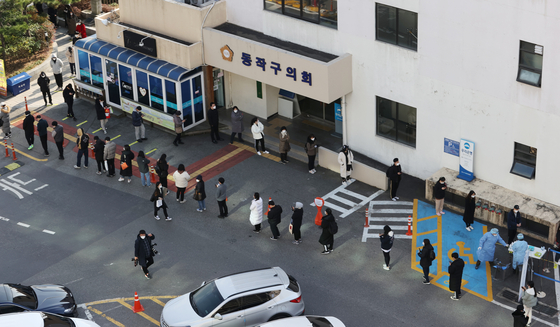 People line up to get tested for Covid-19 at a test center installed at the parking lot of the Dongjak District Office in southern Seoul due to concern over a cluster of cases linked to a nearby Noryangjin cram school and amid a third wave of infections in the country. [YONHAP]