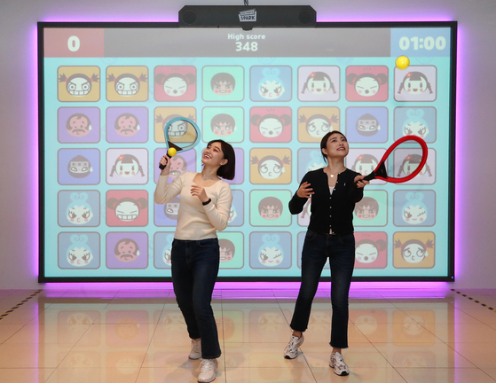 """Models play virtual tennis on the Spark S1, a smart health care system developed by Happy Sketch, at its launch event in Gangnam, southern Seoul, Wednesday. Happy Sketch developed an all-in-one screen module where users can play different sports with characters from the animation """"Puka."""" [YONHAP]"""
