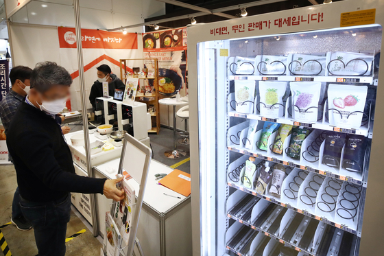 Visitors to the 2020 International Franchise Show in Seoul look at an unmanned vendor at an exhibition booth on Thursday at Coex in Gangnam District, southern Seoul. Hosted by the Korea Franchise Association, the three-day show showcases more than 25 local franchises in a range of industries, including restaurants, services and media, until Saturday afternoon. [YONHAP]