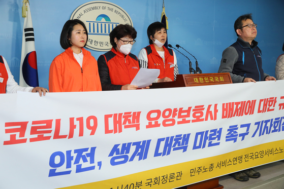 A group of caregivers for the elderly hold a press conference on March 9, 2020, at the National Assembly to urge the government to come up with measures to ensure their job safety and health protections.  [YONHAP]