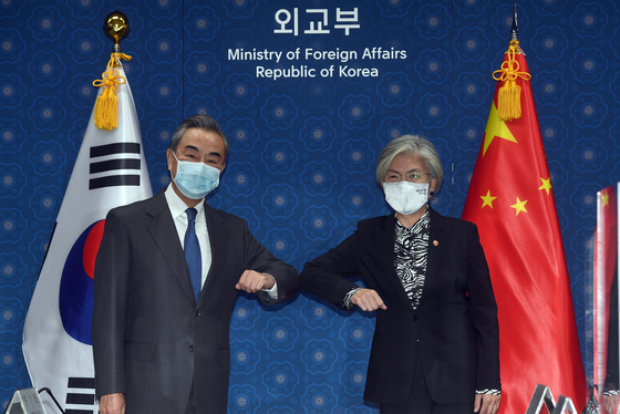 Korean Foreign Minister Kang Kyung-wha, right, and Chinese Foreign Minister Wang Yi bump elbows ahead of talks at the Foreign Ministry in central Seoul Thursday morning. [JOINT PRESS CORPS]