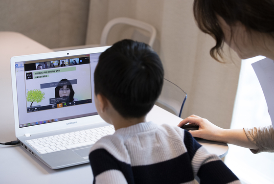 In this file photo, a first grader at Yongsan Elementary School looks into a computer screen with the help of his mother from their home in Yongsan District of central Seoul on April 20, 2020.  [YONHAP]