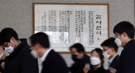 People walk past a framed prosecutors' oath at the Seoul Central District Prosecutors' Office in Seocho District, southern Seoul, Thursday. Prosecutors have been holding meetings to discuss the justice minister's suspension of Prosecutor General Yoon Seok-youl over alleged ethical and legal breaches, with some issuing statements protesting the action. [YONHAP]