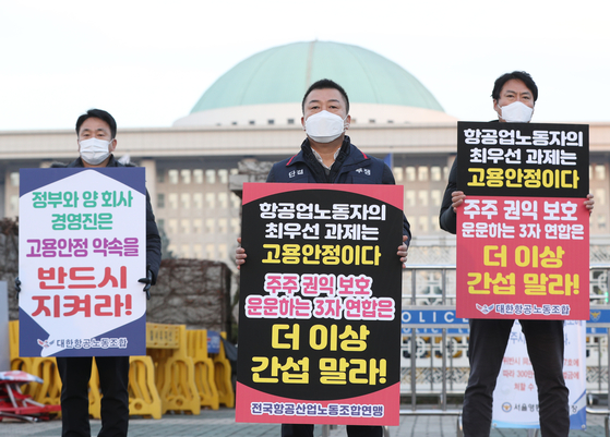 Labor unions members from Asiana Airlines and Korean Air Lines protest the latter's acquisition of the former in Yeouido, western Seoul, on Wednesday. [NEWS1]