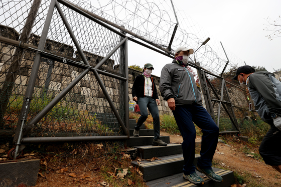 Visitors to the new Mt. Bukak trail walk through a barbed-wire gate that can easily be spotted along the trail. [YONHAP]