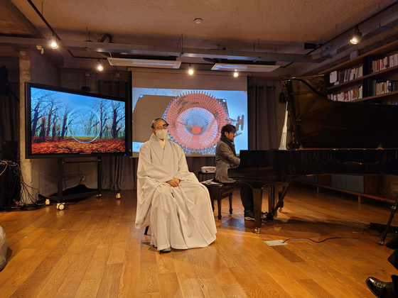 """As part of the """"Neuro-Knitting Beethoven"""" performance by Berlin-based artist duo Varvara & Mar, Korean pianist Jongwha Park plays pieces by Beethoven and Buddhist monk Oh Shim listens while wearing an EEG headset, at Art Center Nabi's laboratory Tazak Madang in central Seoul on Friday evening. [MOON SO-YOUNG]"""