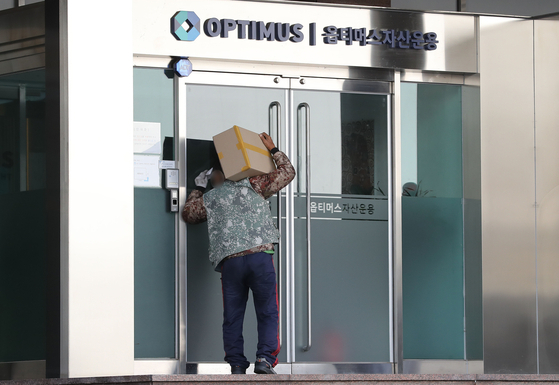 A delivery worker takes a peek at the closed doors of Optimus Asset Management's office in Gangnam, southern Seoul on October 13. [NEWS1]
