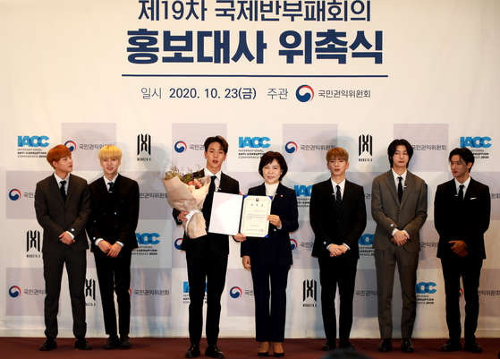 """Jeon Hyun-heui, center right, chairperson of the Anti-Corruption and Civil Rights Commission (ACRC), appoints boy band Monsta X as the """"publicity ambassadors"""" of the International Anti-Corruption Conference (IACC) last month at Coex in Gangnam District, southern Seoul. [ACRC]"""
