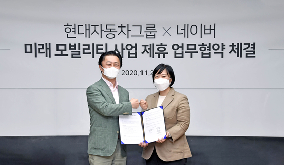 Hyundai Motor President Chi Young-cho, left, and Naver CEO Han Seong-sook pose for a photo after signing an agreement Friday to collaborate on future mobility at Naver Green Factory in Seongnam, Gyeonggi. [HYUNDAI MOTOR]