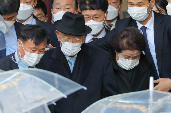 Former President Chun Doo Hwan, center, walks out of the Gwangju District Court accompanied by his wife after the court found him guilty of defaming a priest who was an eye witness to the military crackdown on pro-democracy demonstrators in Gwangju in 1980. [NEWS1]