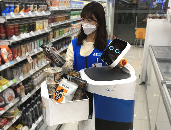 A GS25 employee fills LG Electronics' CLOi robot with items for delivery. [GS25]