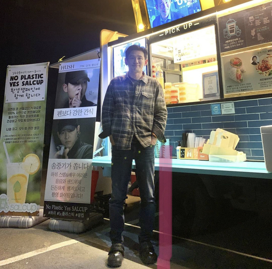 A photo of actor Hwang Jung-min in front of a food truck sent by fellow actor Song Joong-ki, posted by food delivery service Salcup on its Instagram on Monday. [SCREEN CAPTURE]