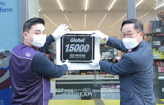 BGF Retail Chairman Lee Keon-jun, right, hangs up a sign in Yatap-dong in Bundang, Gyeonggi, to celebrate the opening of the company's 15,000th CU convenience store on Monday. Lee laid out his vision for the company's future at the event. [YONHAP]