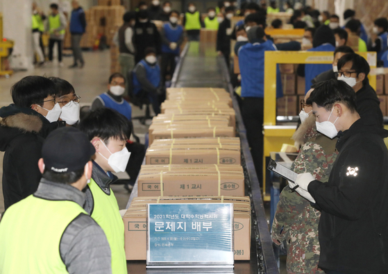 Workers sort boxes of test sheets for this year's College Scholastic Ability Test (CSAT) at a printing factory in Sejong City Monday, three days ahead of the exam. [YONHAP]
