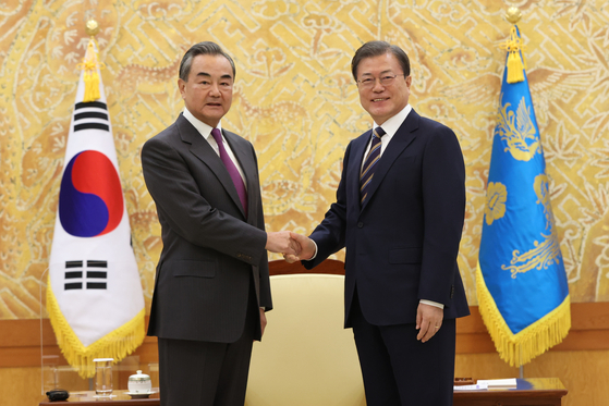 Korean President Moon Jae-in, right, shakes hands with Chinese State Councilor and Foreign Minister Wang Yi at the Blue House in central Seoul Thursday afternoon. [YONHAP]