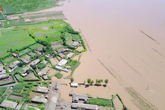 A village in North Hwanghae Province, one of North Korea's most important grain-producing areas, is shown heavily flooded in state media footage from July. The downpours, and the pandemic, aggravated the country's food insecurity this year, but Pyongyang refuses to accept help. [YONHAP]