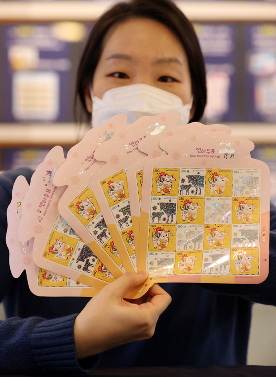 A Korea Post employee holds up next year's stamps with images of a white ox. The year 2021 is the year of the white ox according to the lunar calendar. The year of the ox is usually considered to be a year of peace and leisure. [YONHAP]