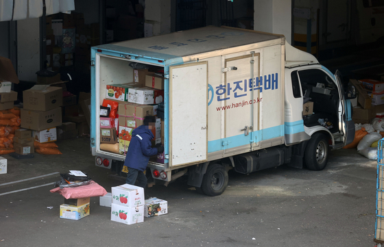 A delivery worker organizing packages inside a delivery truck in Seoul on Tuesday. [YONHAP]