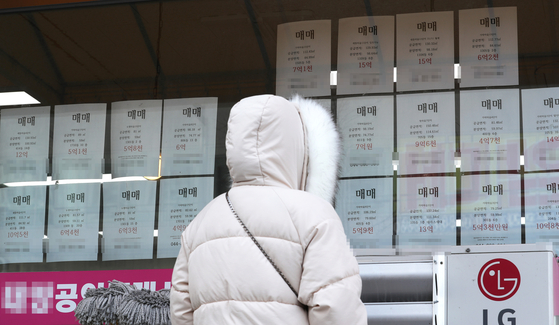 A customer looks at sales postings at a real estate agency in Sejong on Tuesday. According to the Korea Appraisal Board, jeonse long-term rent prices in Sejong rose 4.3 percent last month compared to the previous month. The nationwide jeonse prices jumped the most in seven years. [YONHAP]