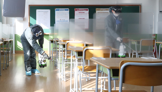 Workers disinfect a classroom at Ulsan Joongang High School in Ulsan Tuesday, two days before it will be used as a testing site for the College Scholastic Ability Test (CSAT). [YONHAP]
