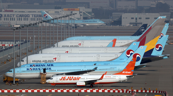 Korean Air and Asiana planes parked at Incheon International Airport on Monday. Korean Air will be acquiring Asiana with help from KDB. [YONHAP]