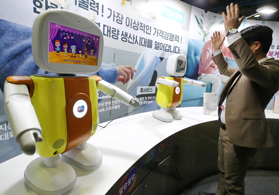 A visitor to a software trade show at Coex in Gangnam District, southern Seoul, tests an artificial intelligence-equipped robot on Wednesday. The trade show runs through Friday. [YONHAP]