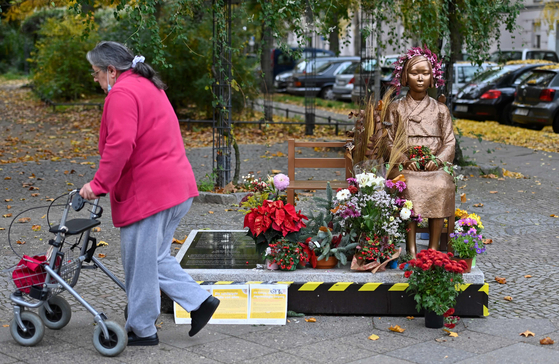 A pedestrian passes a statue representing victims of Japanese wartime sexual slavery that is decorated with flowers in Berlin's Mitte district on Oct. 27. Civic activists fought to retain the 'comfort women' statue after the Japanese government requested its removal to German officials. [AFP/YONHAP]