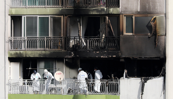 Police and firefighters inspect Wednesday the scene of a fire at an apartment building in Gunpo, Gyeonggi, which led to 11 casualties including four deaths. [NEWS1]