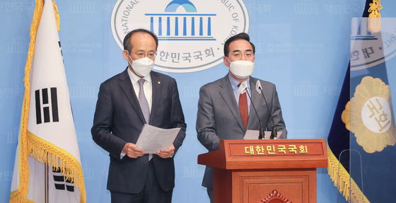From left, People Power Party lawmaker Choo Kyung-ho and Democratic Party lawmaker Park Hong-keun both on the Special Committee on Budget and Accounts announces the agreement made between the two rivaling parties on the 2021 budget at the National Assembly in Yeouido, Seoul, Tuesday. The parties have agreed to pass the budget at the main floor of the National Assembly on Wednesday. If so it would be the first in six years that the budget passes the legal deadline on Dec. 2. [YONHAP]