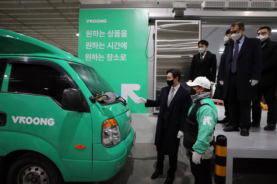 Mesh Korea CEO Rhyu Joung-bum, far left, talks with a delivery driver, at the company's artificial intelligence logistics center in Gimpo, Gyeonggi, on Wednesday. Mesh Korea is the operator of the Vroong last-mile delivery service. It opened two logistics centers in Gimpo and Namyangju, Gyeonggi on Wednesday. [YONHAP]