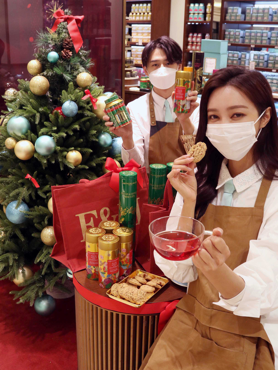 Models pose in front of a Christmas Tree with a holiday-edition tea from Fortnum & Mason on Thursday at a Shinsegae Department Store branch in Gangnam District, southern Seoul. The British tea maker will give out a free jute bag with every 100,000 won ($90) purchase. [SHINSEGAE DEPARTMENT STORE]
