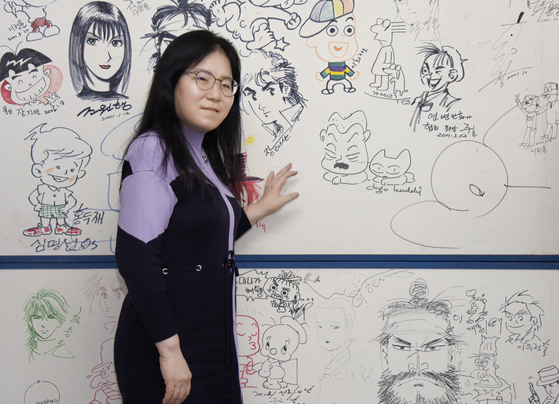 Cartoonist and President of the Korea Cartoonist Association Shin Eel-suk poses in front of a collection of drawings by Korean cartoonists at the association's office located in Seongsu District, eastern Seoul, during an interview with the Korea JoongAng Daily. [JEON TAE-GYU]