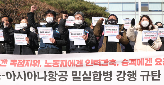 Asiana Airlines labor union members protest their company being acquired by Korean Air Lines in front of Korea Development Bank in Yeouido, western Seoul, on Thursday. [YONHAP]