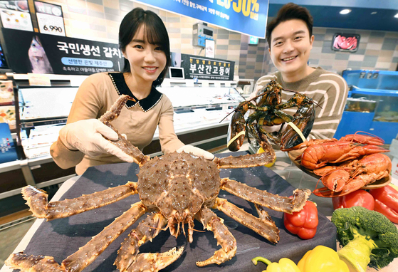 Models promote crabs at the Homeplus Gangseo branch in western Seoul on Thursday. The retailer will hold a Crab Festival, offering customers various types of crabs, such as king crab, lobster and crayfish at discounted prices. The event, which will run through Dec. 23, will be held at all of its branches across the country, as well as online. [YONHAP]