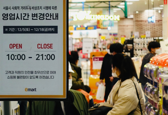 A sign at an Emart store in central Seoul says the store will change operating hours to close at 9 p.m. from Saturday. [YONHAP]