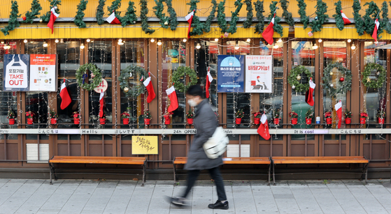 A pedestrian passes a restaurant decorated with Christmas ornaments in the neighborhood of Hongik University in Mapo District, western Seoul, on Monday. As the Level 2.5 social distancing measures are imposed in the capital area, shopkeepers worry that year-end revenues will vanish. [YONHAP]