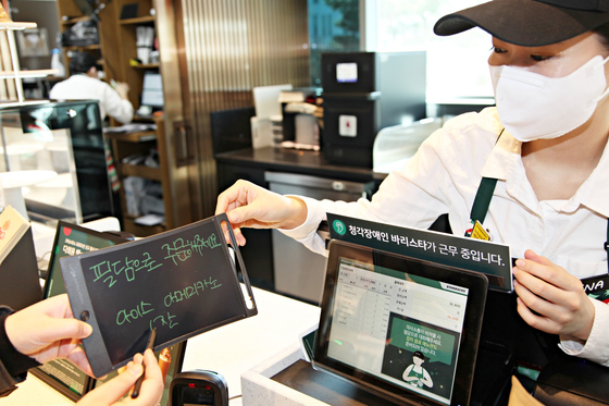 An employee from Starbucks Korea receives an order from a customer who orders an Iced Americano through an electronic notepad. [STARBUCKS KOREA]