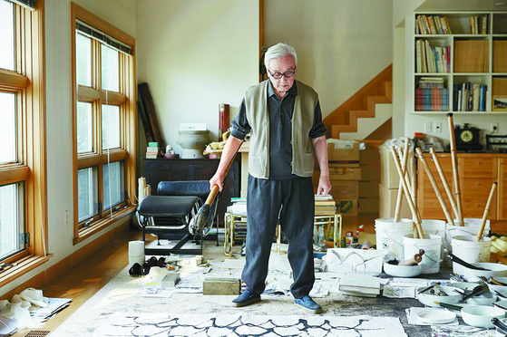"""This photo by Lee Joo-yeon shows artist Suh Se Ok working on one of his """"People"""" series at his studio in central Seoul. [LEHMANN MAUPIN]"""