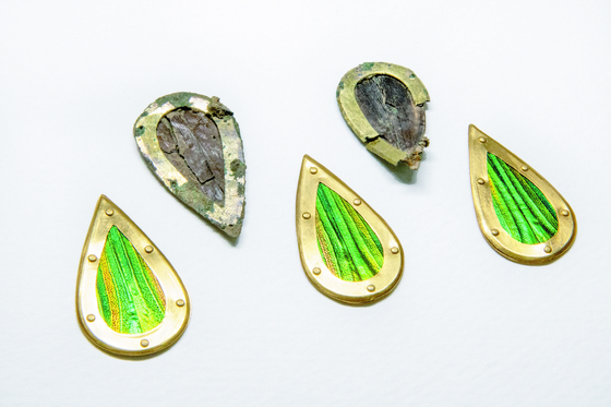 Jewel beetle ornaments were recently excavated at Tomb No. 44 at Jjoksaem in Gyeongju, North Gyeongsang. Bright-colored ones below are their replicas made for reference. [CULTURAL HERITAGE ADMINISTRATION]