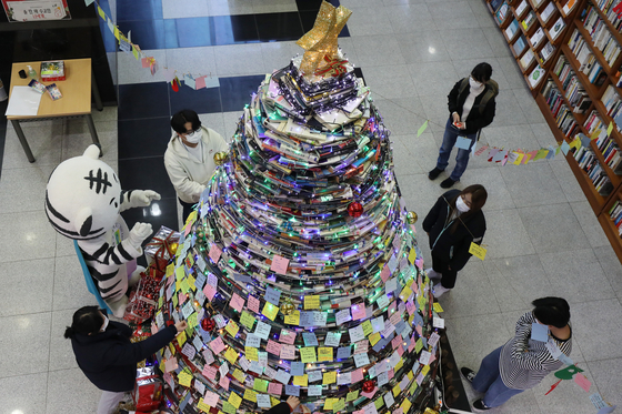 "College students from Daegu University construct a Christmas tree by stacking up 3,000 discarded books in the lobby of the Daegu campus's main library on Tuesday. Students attached hundreds of notes to the ""book tree."" [NEWS1]"