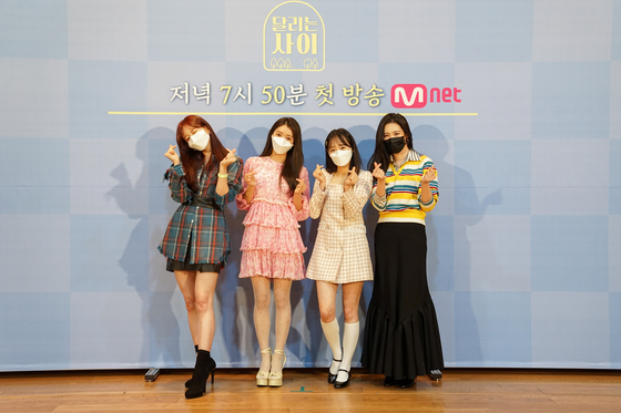 """Singer Sunmi and girl group members Hani of EXID, YooA of Oh My Girl and Chuu of Loona pose for the camera at an online press event for Mnet's new reality show """"Running Girls"""" on Tuesday. [MNET]"""