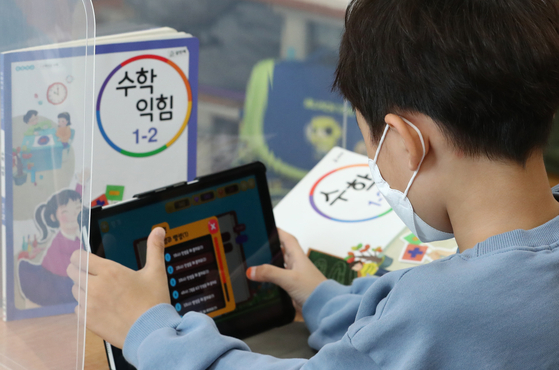 An elementary student listens to a math lesson through a tablet computer. [NEWS1]