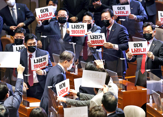 """As President Moon Jae-in leaves the main hall of the National Assembly after delivering the 2021 budget speech, lawmakers of the opposition People Power Party show him protesting signs, asking """"What happened to this country?"""" on Wednesday. [YONHAP]"""