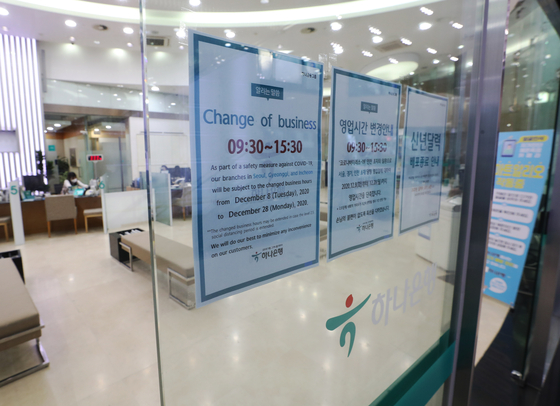 A notice about changed business hours is put up at Hana Bank's headquarters in Jung District, central Seoul, on Tuesday. Due to Level 2.5 social distancing, the operating hours of banks in greater Seoul have been reduced to between 9:30 a.m. and 3:30 p.m. until Dec. 28. [YONHAP]