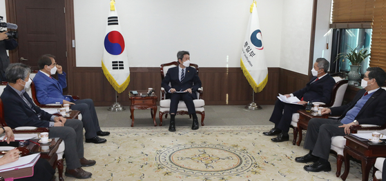 Unification Minister Lee In-young, center, meets with an association of private organizations pursuing cooperative projects with North Korea at the Central Government Complex in central Seoul on Friday. [YONHAP]