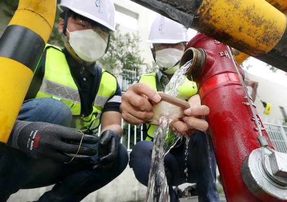 Officials inspect the water pipes and fire hydrant in Gyeyang District in Incheon Monday after larvae-like organisms were found in the city's tap water. [YONHAP]