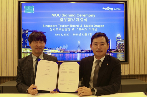 Yoo Bong-yeol, the head of content IP department, left, and CEO Kang Chul-gu of Studio Dragon pose for the camera with the memorandum of understanding signed by the local production house and the Singapore Tourism Board. [SINGAPORE TOURISM BOARD]
