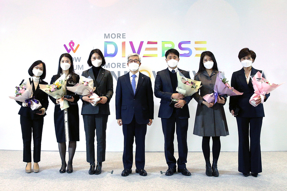 Song Yong-dok, vice chairman of Lotte, poses with six employees recognized at the WOW Forum at the Lotte World Tower in Jamsil, southern Seoul, on Thursday. [LOTTE]