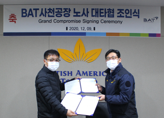 Kang Seung-ho, head of BAT Korea's Sacheon factory, right, and Koo Sung-il, head of the labor union, pose during a compromise signing ceremony which was held at the factory in South Gyeongsang on Wednesday. [BAT KOREA]