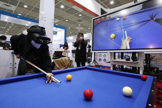 A visitor at the Korea VR Festival plays a billiards game using augmented reality glasses at the booth of the Korea University of Technology and Education. The three-day event took off at Coex in Gangnam, southern Seoul, on Thursday. Due to the coronavirus, visitors were limited to 600 people and conferences were streamed live. [YONHAP]
